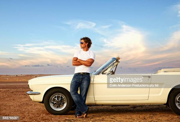 Caucasian man relaxing on convertible on remote road