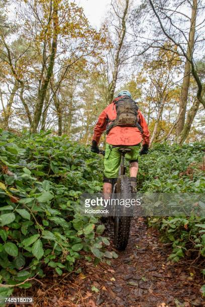 Caucasian man riding bicycle in forest
