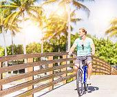 Caucasian man riding bicycle on bridge