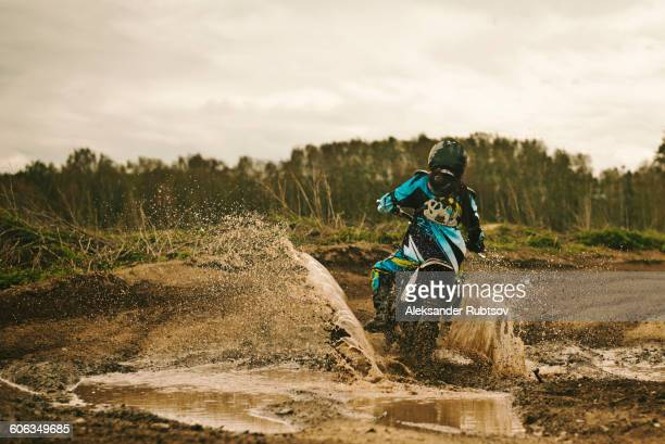 Caucasian man riding dirt bike in puddle