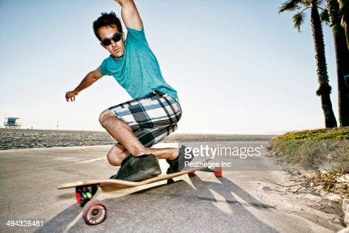 Caucasian man riding longboard on beach