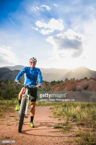 Caucasian man riding mountain bike on dusty path