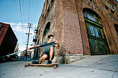 Caucasian man riding skateboard with land paddle