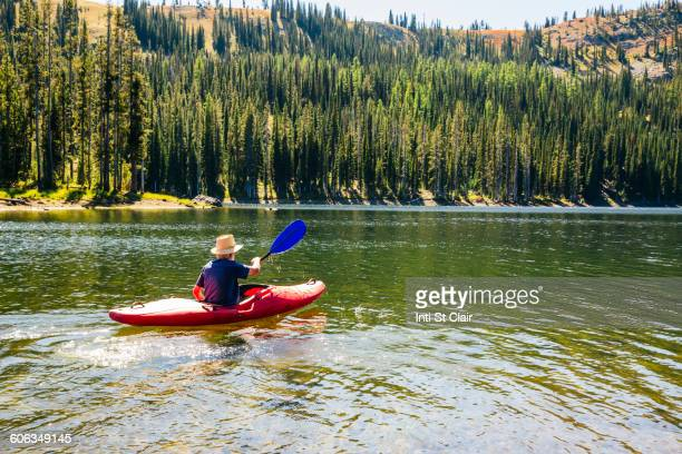 Caucasian man rowing canoe on remote lake
