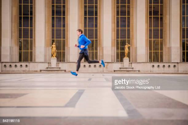 Caucasian man running in courtyard