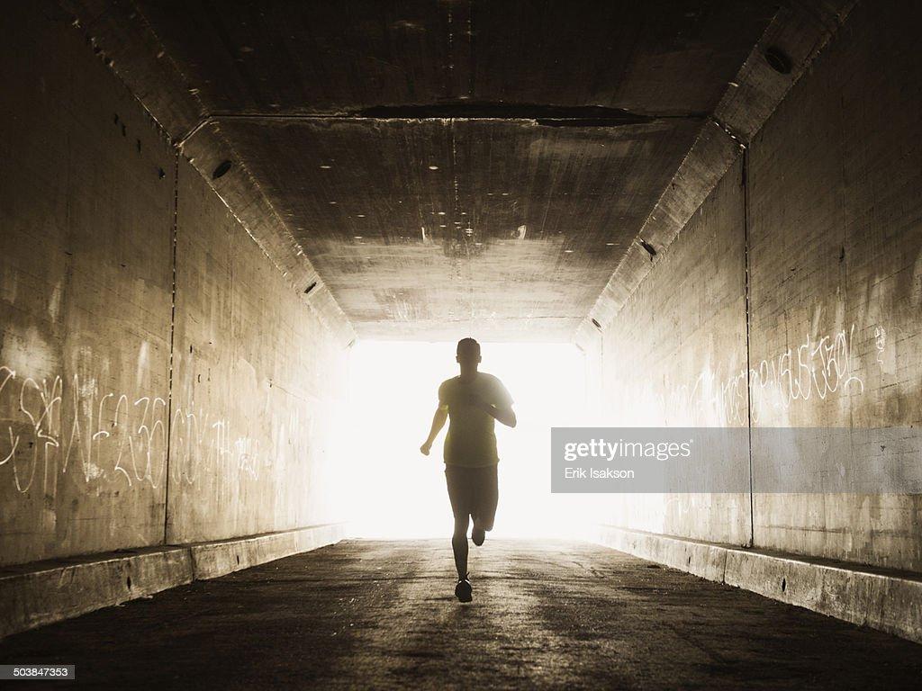 Caucasian man running in urban tunnel : Foto stock