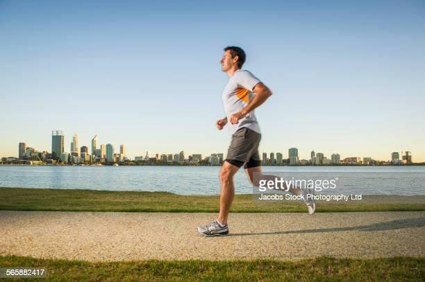 Caucasian man running near urban waterfront, Perth, Western Australia, Australia