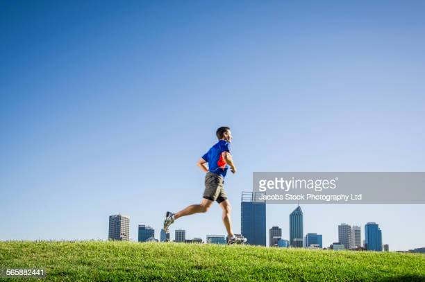 Caucasian man running on grassy hill near Perth city skyline, Western Australia, Australia