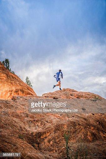 Caucasian man running on rock formation