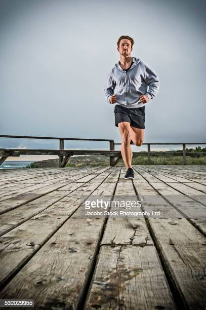Caucasian man running on wooden boardwalk