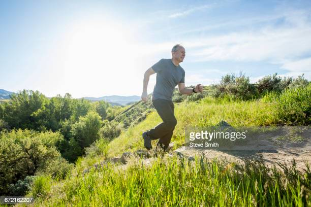 Caucasian man running up staircase on hill