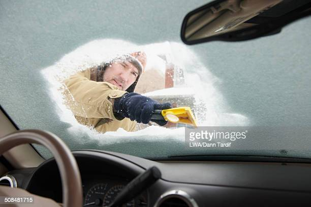 Caucasian man scraping snow off car windshield