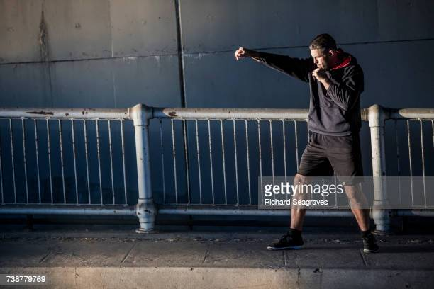 Caucasian man shadow boxing near railing