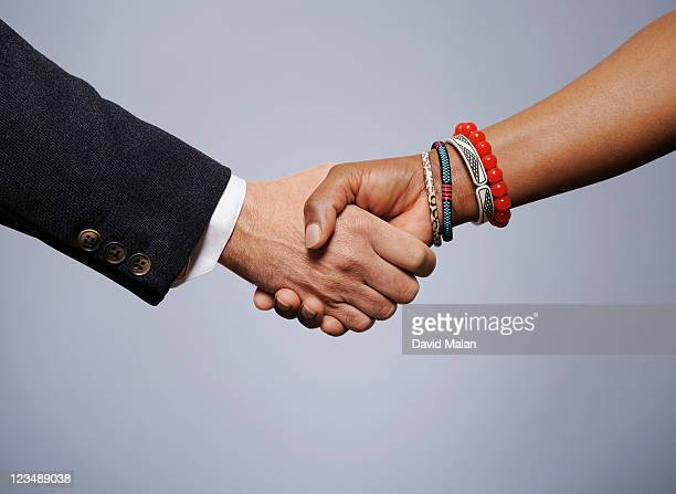 Caucasian man shaking hands with an African woman