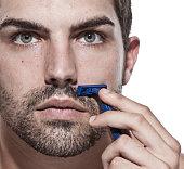 Caucasian man shaving his beard