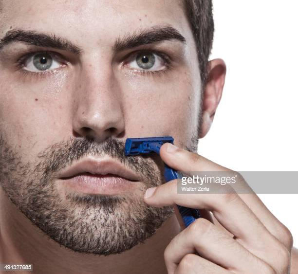 Caucasian man shaving his beard