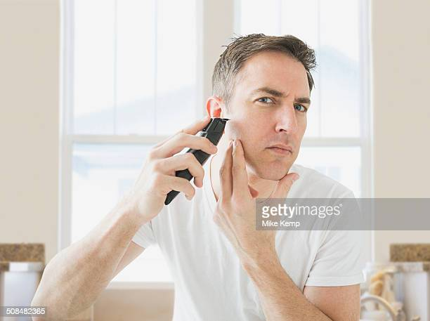 Caucasian man shaving in bathroom