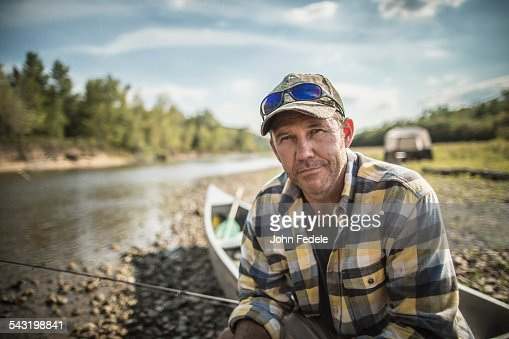 Caucasian man sitting in canoe on riverbed