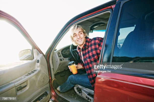 Caucasian man sitting in cat holding coffee cup