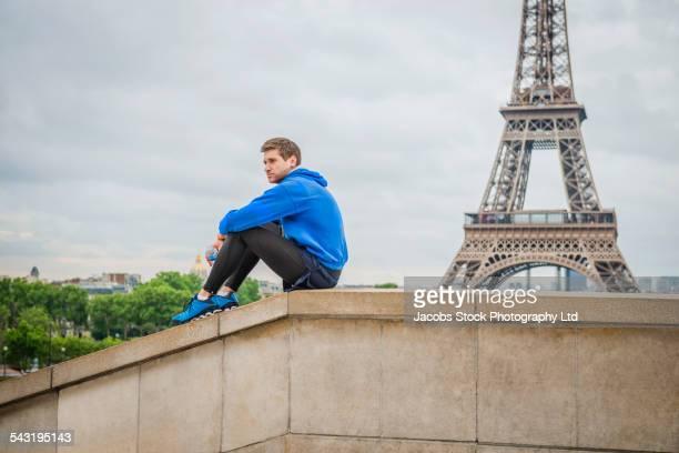 Caucasian man sitting near Eiffel Tower, Paris, France