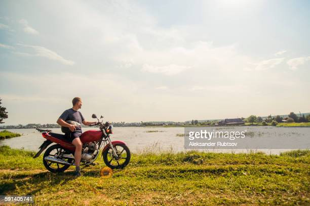 Caucasian man sitting on motorcycle in park