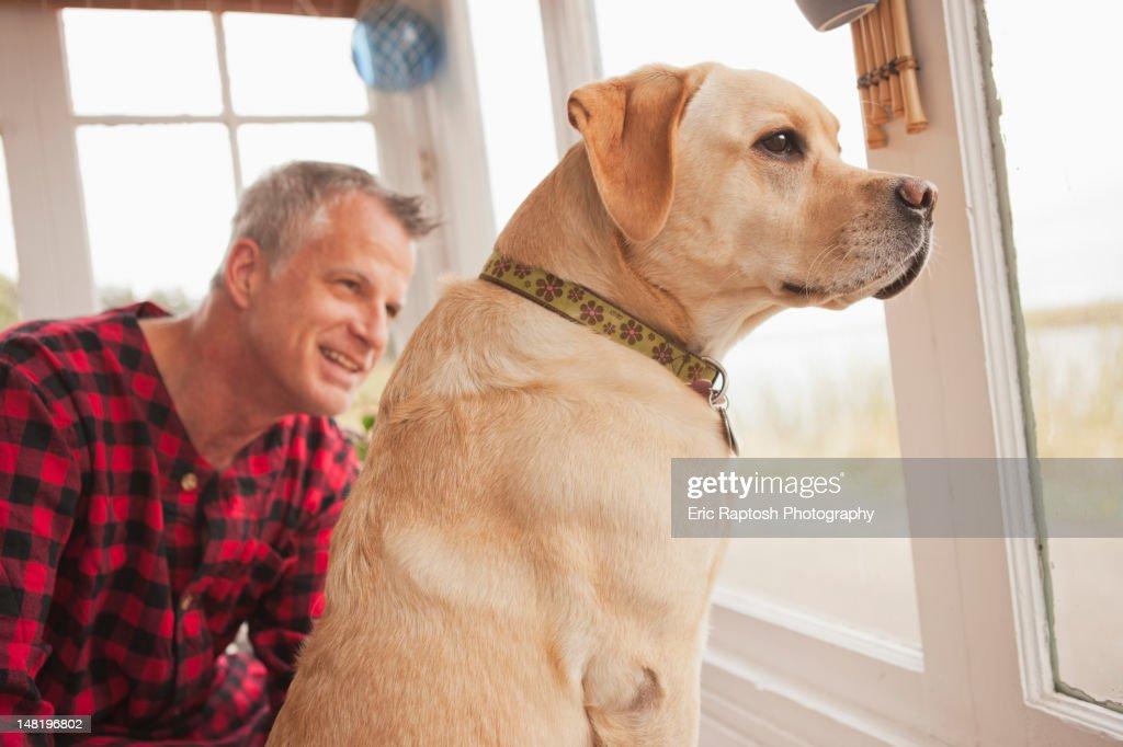 Caucasian man sitting with labrador : Stock Photo