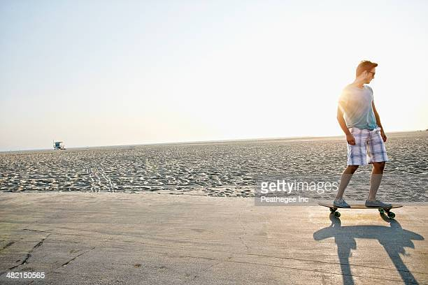 Caucasian man skating on beach