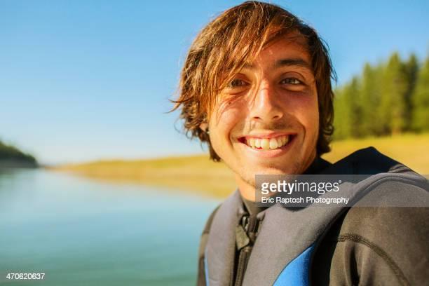 Caucasian man smiling by rural lake