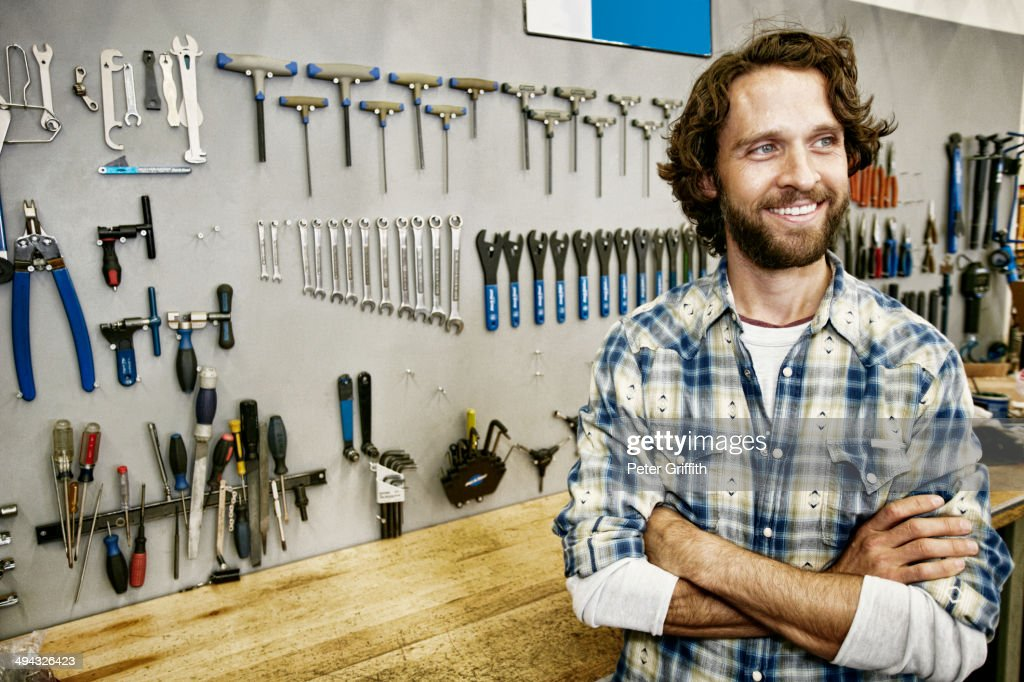 Caucasian man smiling in bicycle repair shop