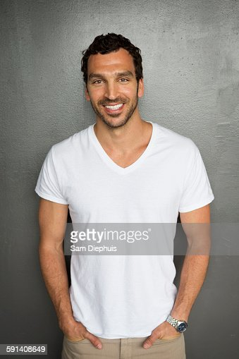 Caucasian man smiling with hands in pockets
