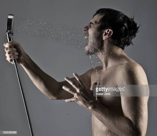 Caucasian man spraying himself in the face with shower