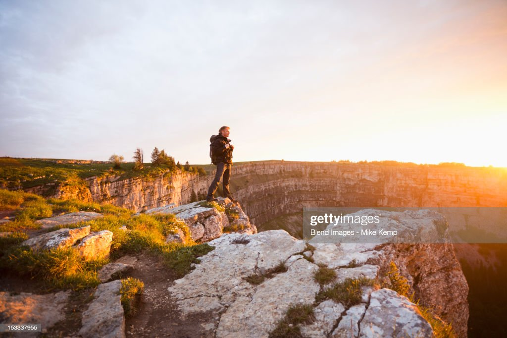 Caucasian man standing on remote cliff