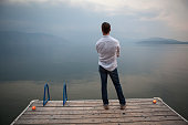 Caucasian man standing on wooden dock over lake