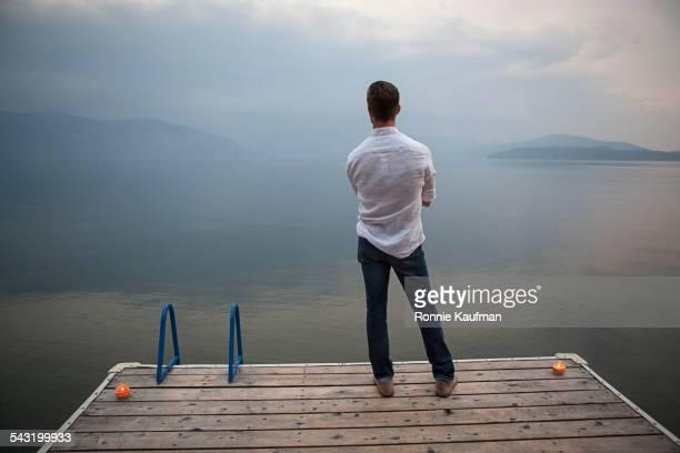Caucasian man standing on wooden dock over lake