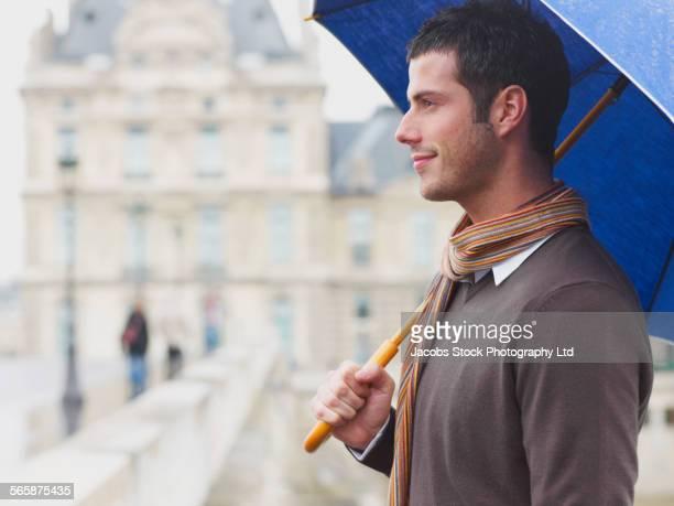 Caucasian man standing under umbrella on urban bridge