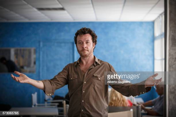 Caucasian man standing with arms outstretched in living room