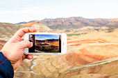 Caucasian man taking cell phone photograph of desert landscape, Painted Hills, Oregon, United States