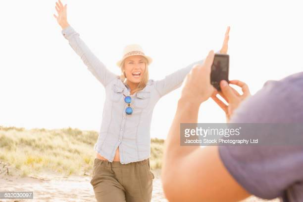 Caucasian man taking cell phone photograph of girlfriend on beach