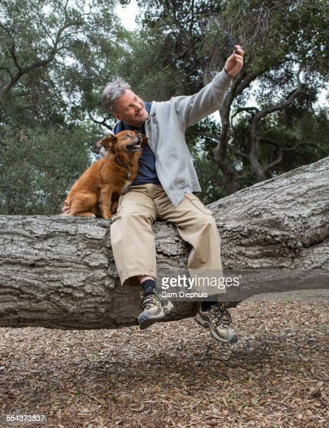 Caucasian man taking cell phone photograph with dog on tree in park