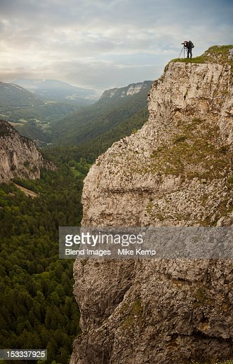 Caucasian man taking photographs from edge of cliff