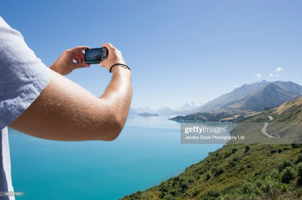 Caucasian man taking picture of rural landscape : Stock Photo