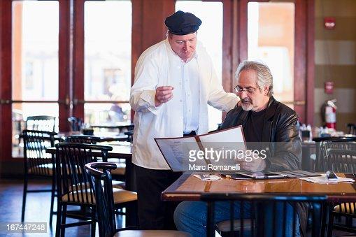 Caucasian man talking to chef in restaurant : Stock Photo