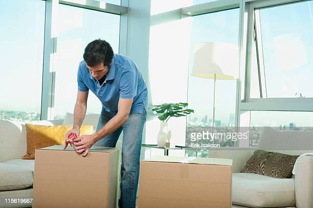 Caucasian man taping cardboard box in living room