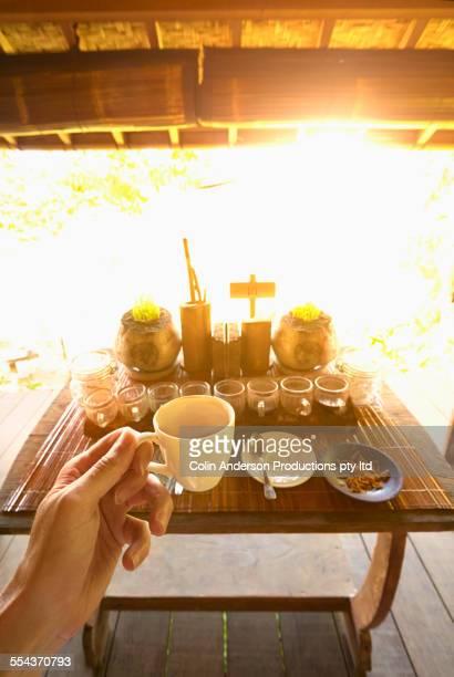 Caucasian man tasting sample of coffee and tea