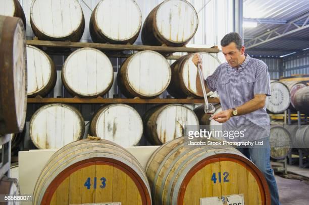 Caucasian man tasting wine in winery