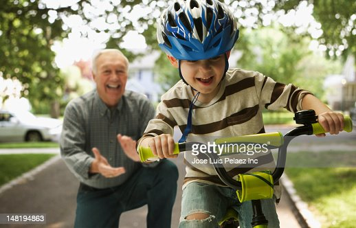 Caucasian man teaching grandson to ride a bicycle