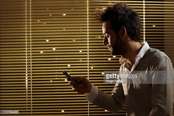 Caucasian man text messaging on cell phone at night