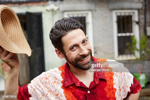 Caucasian man tipping straw hat in backyard
