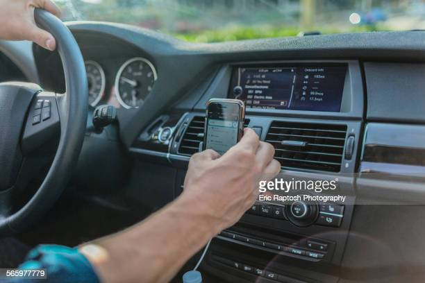 Caucasian man using cell phone and driving car