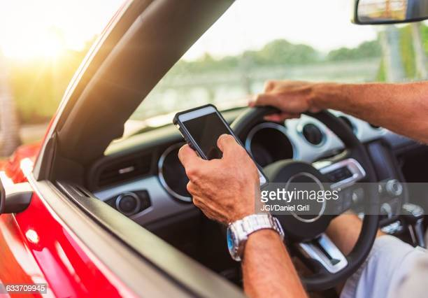 Caucasian man using cell phone and driving convertible